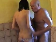 Young brunette hair helps grand-dad take a shower and dries his penis with her throat